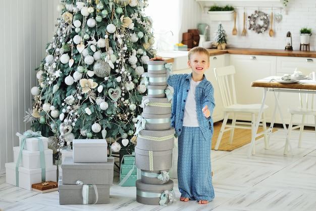 Un bambino, un ragazzino in pigiama blu, sta a piedi nudi sullo sfondo di un albero di natale e tiene in mano molti doni.
