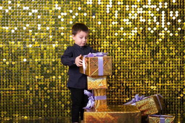 Bambino sorridente con scatola regalo su sfondo con paillettes dorate lucide, paillettes.