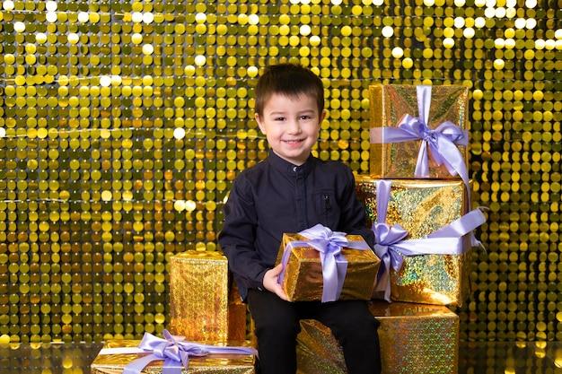 Bambino sorridente che tiene in mano una scatola regalo sullo sfondo con paillettes di paillettes dorate lucide