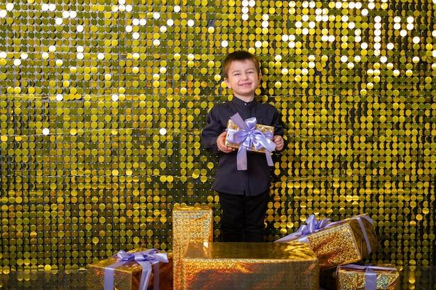 Bambino sorridente che tiene in mano una confezione regalo su sfondo con paillettes dorate lucide, paillettes.