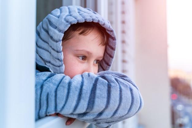 Il bambino si alza e guarda fuori dalla finestra
