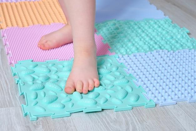 Il bambino si leva in piedi sulla stuoia di massaggio del piede