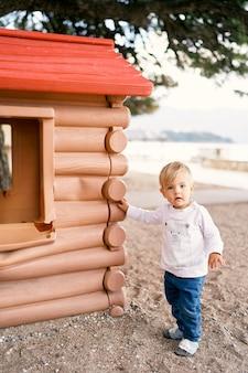 Il bambino sta vicino a una casa giocattolo nel parco giochi