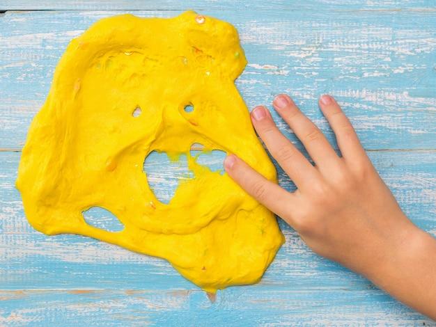Il bambino stende la sua faccia della mano destra di melma gialla su un tavolo blu. giocattolo antistress. giocattolo per lo sviluppo delle capacità motorie della mano.