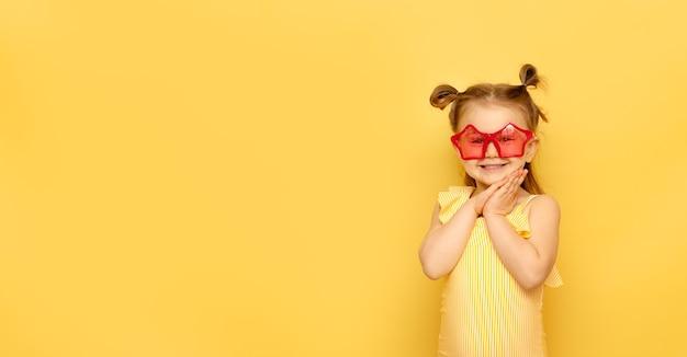 Il bambino in costume da bagno a strisce e occhiali da sole rossi divertenti estivi esamina la macchina fotografica che posa sulla parete gialla