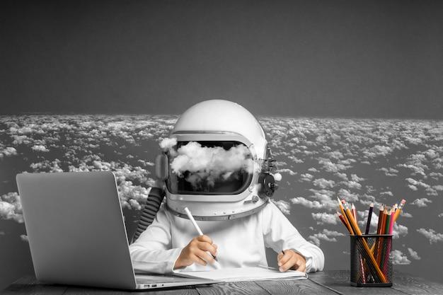 Il bambino studia a distanza a scuola, indossando un casco da astronauta. di nuovo a scuola