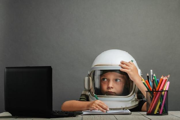 Il bambino studia a scuola a distanza, indossando un casco da astronauta. di nuovo a scuola