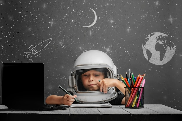 Il bambino studia a scuola a distanza, indossando un casco da astronauta.
