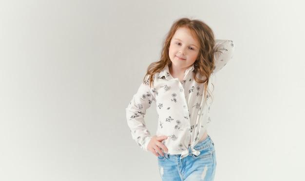 Il bambino in studio in posa con abiti alla moda