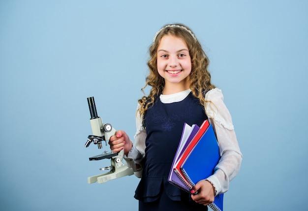 Lezione di biologia dello studio del bambino. scopri il futuro. educazione e conoscenza. ricerca scientifica in laboratorio. piccola ragazza geniale con microscopio. di nuovo a scuola. test di scienziata piccola ragazza. lezione a scuola.