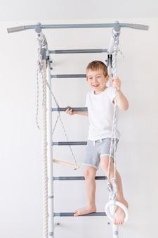 Un bambino sul muro svedese fa sport a casa, un ragazzo sale una scala con una corda, il concetto di sport e salute