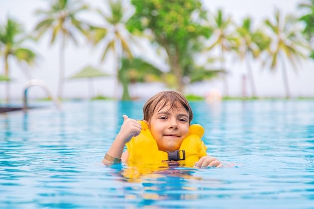 Il bambino nuota in piscina in estate. messa a fuoco selettiva.