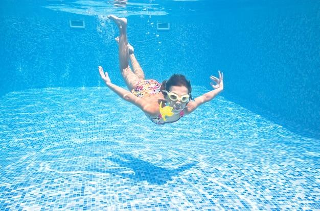 Il bambino nuota sott'acqua in piscina la ragazza attiva si tuffa e si diverte sott'acqua fitness per bambini