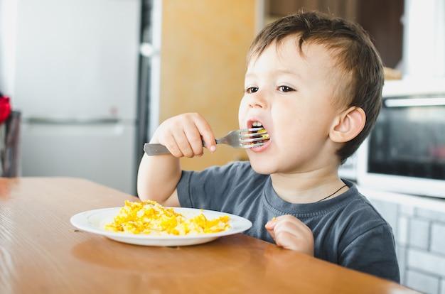 Un bambino in maglietta in cucina che mangia una frittata, forchetta da solo