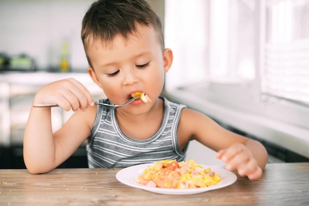 Un bambino in maglietta in cucina che mangia una frittata con salsiccia e pomodori con una forchetta