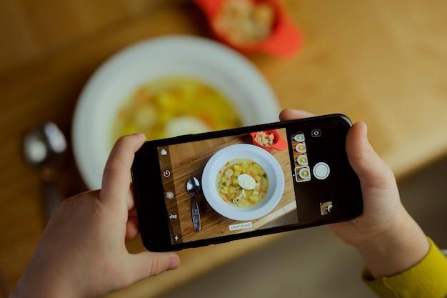 Il bambino scatta una foto del cibo su uno smartphone