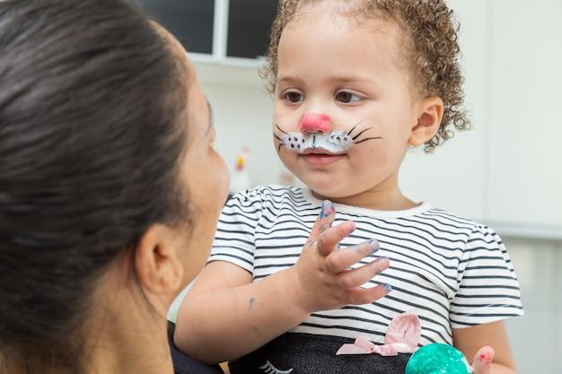 Bambino che parla con tia e il suo viso con la vernice del coniglietto di pasqua.
