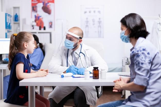 Bambino che parla con il pediatra durante la consultazione nell'ufficio dell'ospedale. medico specialista che fornisce servizi di assistenza sanitaria consulenze trattamento in dispositivi di protezione.