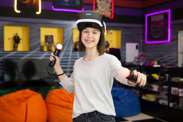 Bambino, un'adolescente che gioca su una console di gioco con occhiali per realtà virtuale che spara a un gioco con una pistola telecomandata in un club di gioco. vr