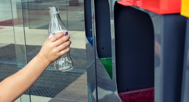 Il bambino getta la bottiglia di vetro in uno dei quattro contenitori per lo smistamento dei rifiuti