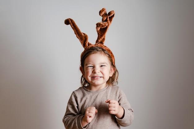 Bambino del bambino con la fascia dei cervi a casa con il fronte divertente uscito. vacanze di natale capodanno