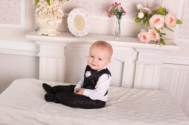 Bambino in smoking, seduto sul letto accanto al caminetto. lo sposo.
