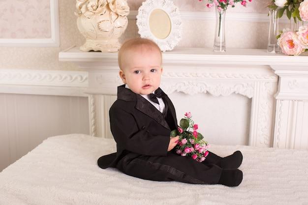 Bambino in smoking seduto sul letto accanto al camino con fiori in mano.