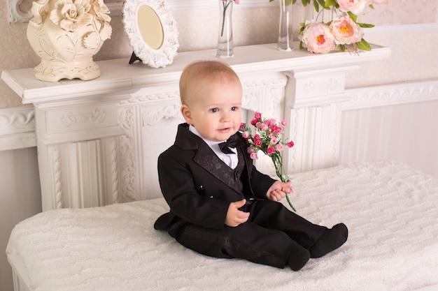 Bambino in smoking seduto sul letto accanto al caminetto con fiori in mano.