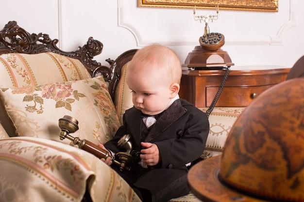 Bambino in smoking seduto in un ufficio a parlare al telefono.