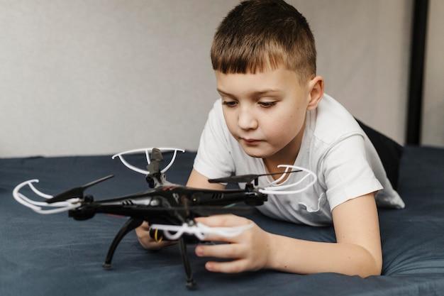 Bambino che usa un drone e sta a letto