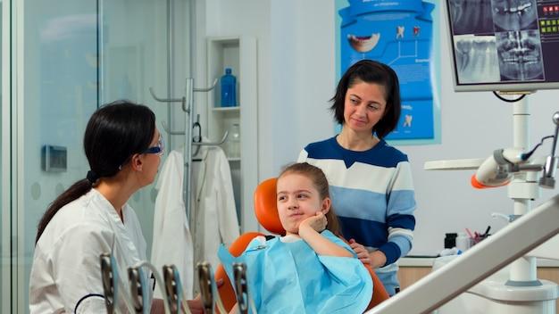 Bambino che usa il dito per puntare il dente affetto mentre il dentista parla con la madre del mal di denti orale. medico di odontoiatria che spiega alla mamma il processo dentale, figlia seduta su una sedia stomatologica
