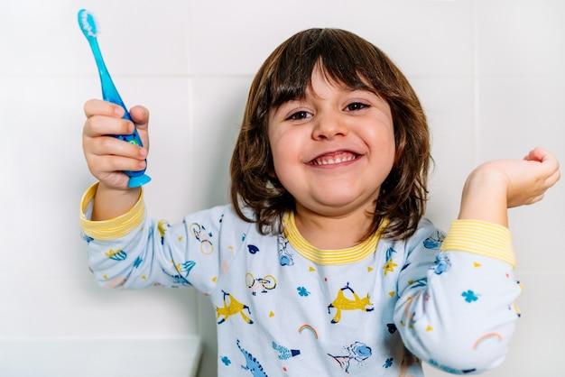 Bambino molto allegro dopo aver lavato i denti con uno spazzolino da denti con il pigiama prima di andare a letto