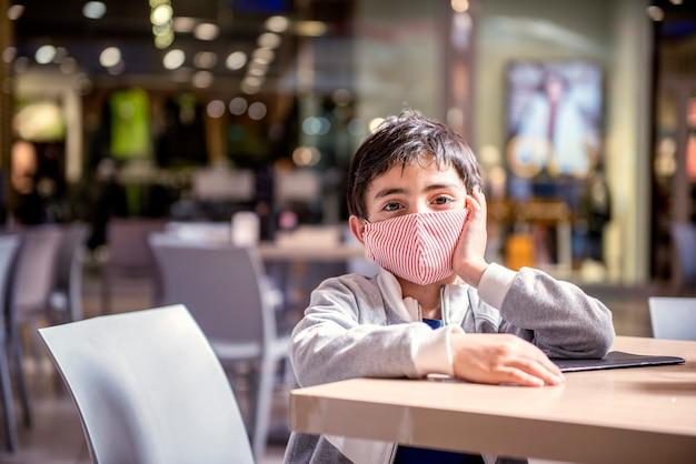 Il bambino aspetta al tavolo del ristorante del centro commerciale indossando una maschera protettiva