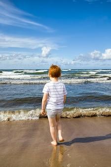 Bambino che cammina sulla riva