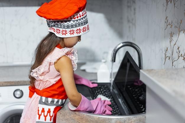Il bambino lava il laptop nel lavandino in cucina