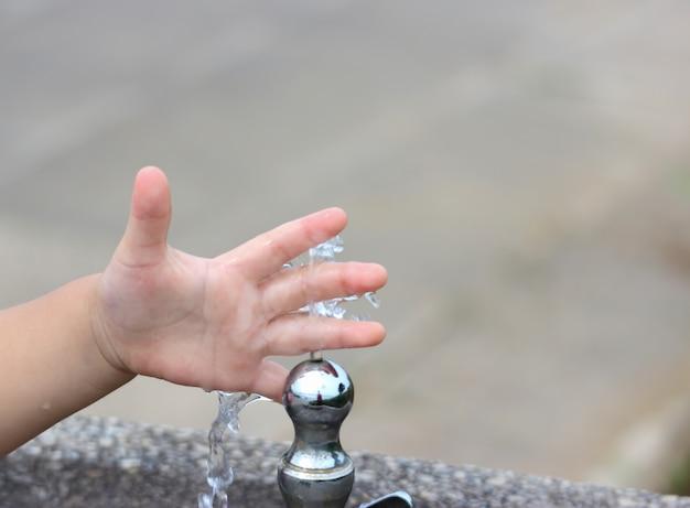 Una mano di lavaggio del bambino dall'acqua dal rubinetto giapponese in parco pubblico.