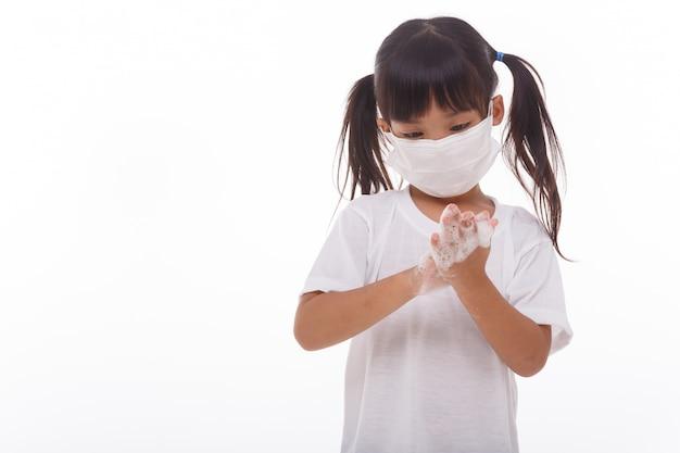 Mani di lavaggio del bambino e mostrare le palme insaponate su bianco