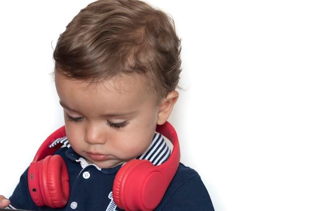 Bambino che guarda i video sul cellulare con cuffie rosse e maglietta blu scuro