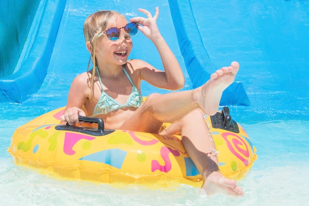 Bambino su scivolo d'acqua al parco acquatico. vacanze estive.