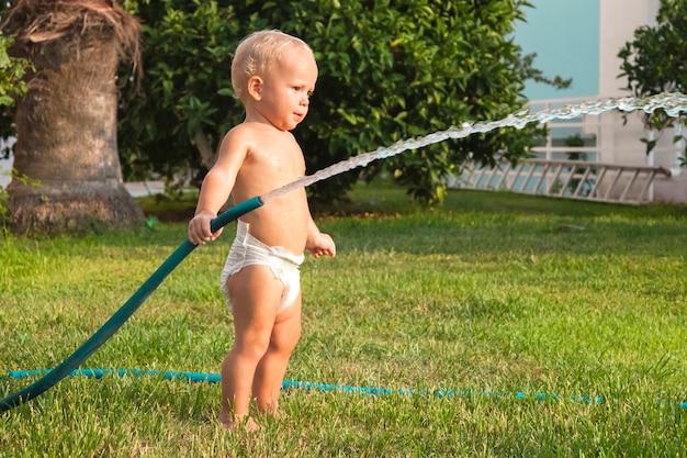 Bambino che innaffia l'erba nel cortile