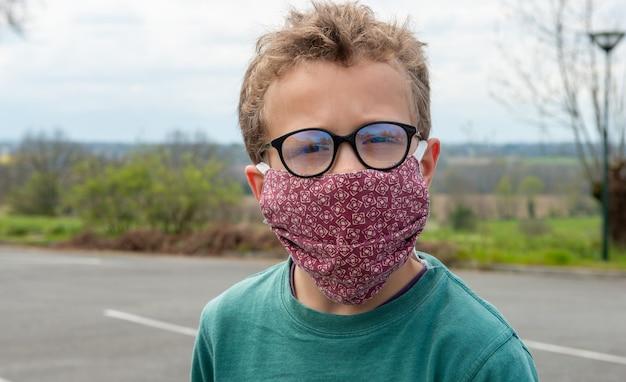 Bambino che indossa la maschera anti virus all'aperto