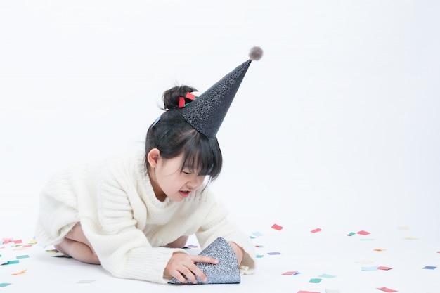Il bambino che indossa un cappello da festa nero si sta divertendo. sfondo bianco e cappello nero vanno bene insieme.