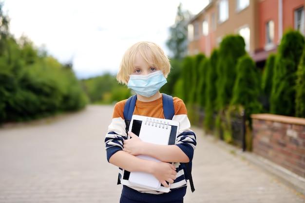 Bambino che indossa la maschera per il viso andando a riaprire la scuola