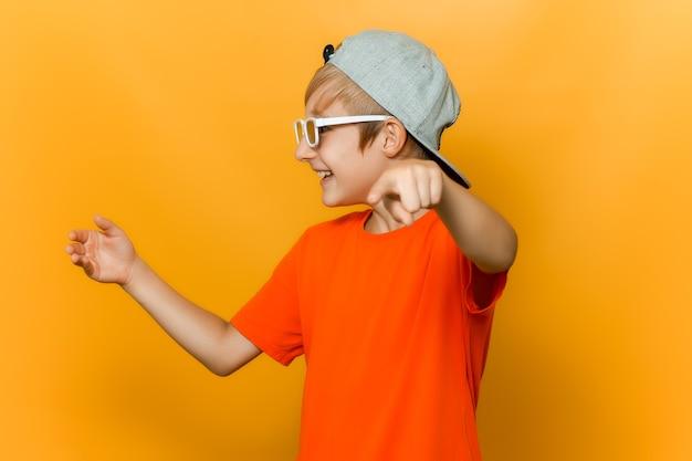 Un bambino con gli occhiali per guardare i film guarda di lato e punta il dito in avanti e prende in giro