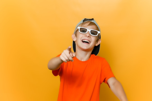 Un bambino con gli occhiali per guardare i film punta il dito in avanti e prende in giro