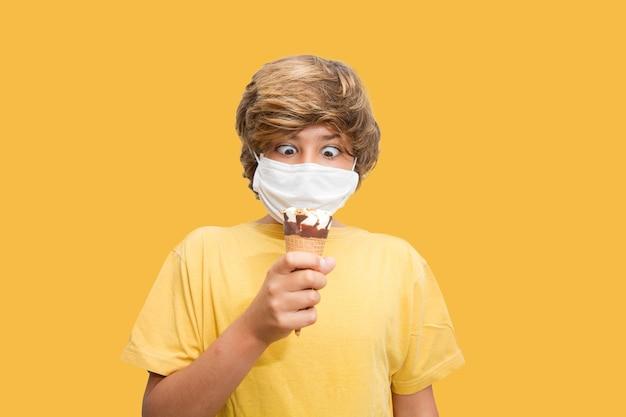 Il bambino che indossa una maschera vuole mangiare il gelato anche se ha la maschera addosso