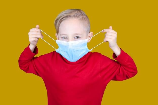 Il bambino indossa una mascherina medica su sfondo giallo