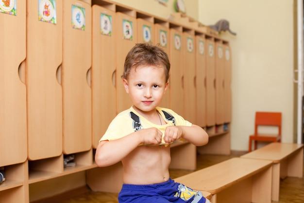 Il bambino indossa una maglietta all'asilo