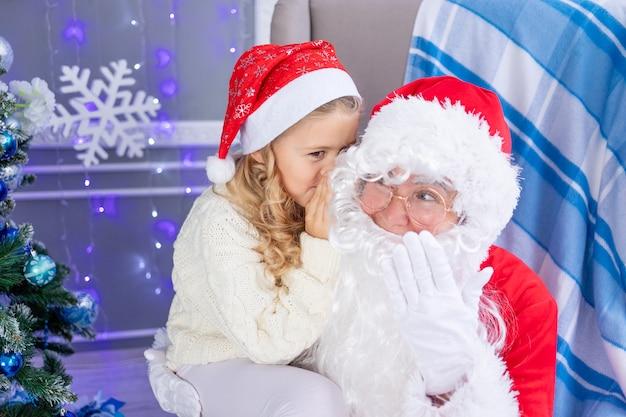 Un bambino sussurra un desiderio all'orecchio di babbo natale, babbo natale legge una lettera all'albero di natale, il concetto di nuovo anno e natale