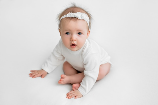 Un bambino su uno sfondo bianco alza gli occhi con la bocca aperta.